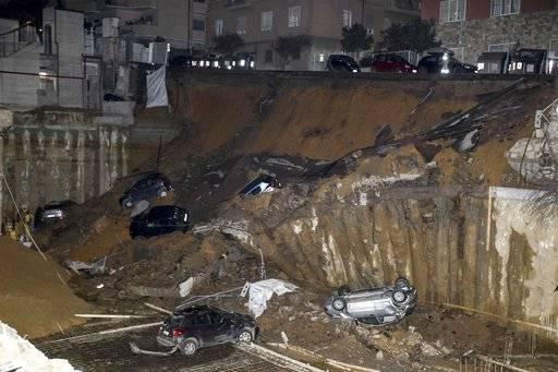 A view of a large sinkhole that opened in a street of a residential area in Rome, Wednesday Feb. 14, 2018. Various cars fell in the chasm and two buildings were temporarily evacuated as a precautionary measure after the collapse. (Massimo Percossi/ANSA via AP)