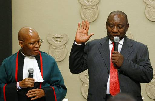 Cyril Ramaphosa is sworn in as South African President by Chief Justice Mogoeng Mogoeng, left, in Cape Town, South Africa Thursday Feb. 15, 2018. Ramaphosa on Thursday was elected unopposed as South Africa's new president by ruling party legislators after the Wednesday resignation of Jacob Zuma. (Mike Hutchings / Pool via AP)