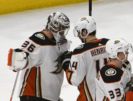 Anaheim Ducks goaltender John Gibson (36) and center Adam Henrique (14) celebrate their win over the Chicago Blackhawks in an NHL hockey game Thursday, Feb. 15, 2018, in Chicago. (AP Photo/David Banks)
