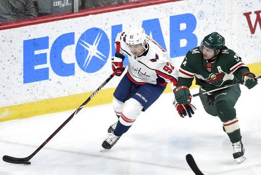 Washington Capitals' Evgeny Kuznetsov (92), of Russia, carries the puck as Minnesota Wild left wing Zach Parise (11) defends during the first period of an NHL hockey game Thursday, Feb. 15, 2018, in St. Paul, Minn. (AP Photo/Hannah Foslien)