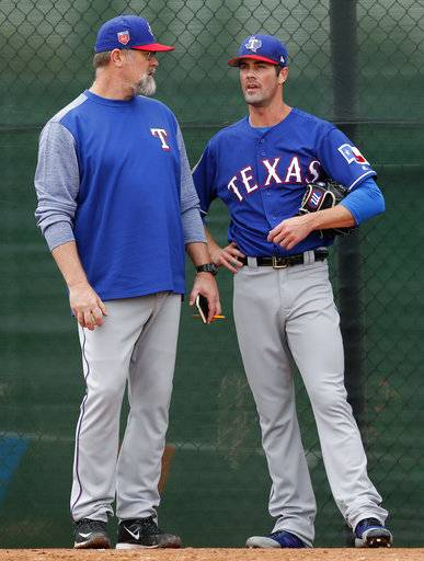 Texas Rangers pitching coach Doug Brocail, left, talks with pitcher Cole Hamels during a baseball spring training workout, Thursday, Feb. 15, 2018, in Surprise, Ariz. (AP Photo/Charlie Neibergall)