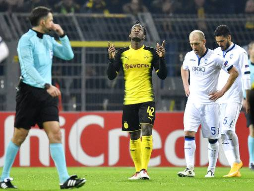 Dortmund's scorer Michy Batshuayi celebrates beside Atalanta's Andrea Masiello and Jose Luis Palomino after winning the Europa League soccer match between Borussia Dortmund and Atalanta Bergamo in Dortmund, Germany, Thursday, Feb. 15, 2018. (AP Photo/Martin Meissner)