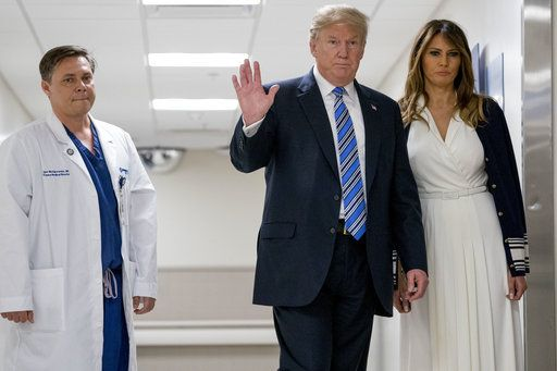 President Donald Trump, center, accompanied by first lady Melania Trump, right, and Dr. Igor Nichiporenko, left, waves to reporters while visiting with medical staff at Broward Health North in Pompano Beach, Fla., Friday, Feb. 16, 2018, following Wednesday's shooting at Marjory Stoneman Douglas High School, in Parkland, Fla.