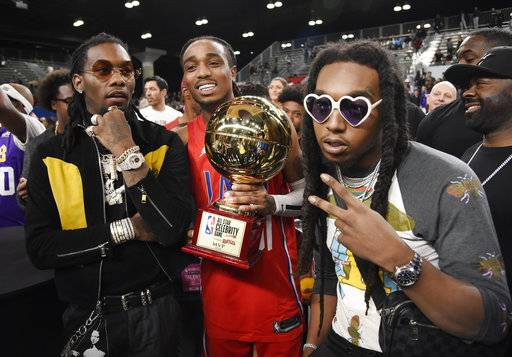 Rapper Quavo, center, the MVP of the NBA All-Star celebrity basketball game, holds his trophy as he poses with his Migos bandmates Offset, left, and Takeoff following the game Friday, Feb. 16, 2018, in Los Angeles.