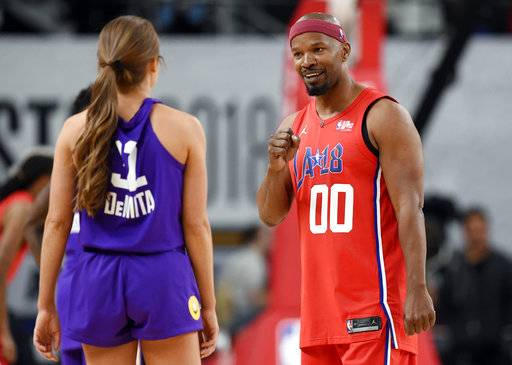 Actor Jamie Foxx, right, of Team Clippers, banters with with TV personality Rachel DeMita, of Team Lakers, during the NBA All-Star celebrity basketball game Friday, Feb. 16, 2018, in Los Angeles.