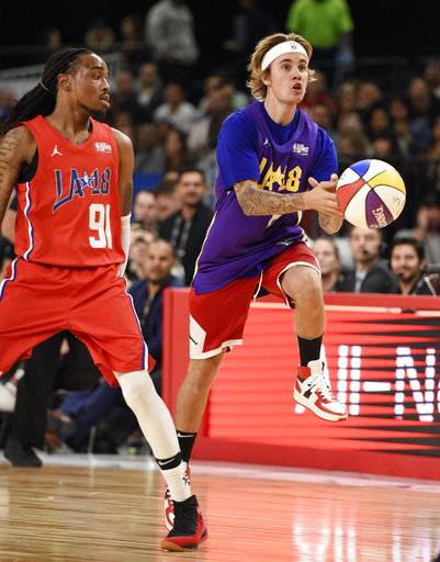 Musician Justin Bieber, right, of Team Lakers, loses the handle on the ball as he leaps past musician Quavo, of Team Clippers, during the NBA All-Star celebrity basketball game Friday, Feb. 16, 2018, in Los Angeles.