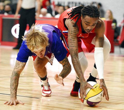 Musician Justin Bieber, left, of Team Lakers, and musician Quavo, of Team Clipper,s go for a loose ball during the NBA All-Star celebrity basketball game Friday, Feb. 16, 2018, in Los Angeles.