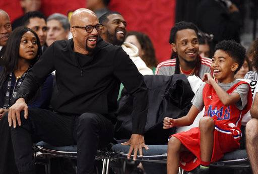 Musician Common, left, one of the coaches of Team Clippers, laughs with actor Miles Brown on the bench during the NBA All-Star celebrity basketball game Friday, Feb. 16, 2018, in Los Angeles.