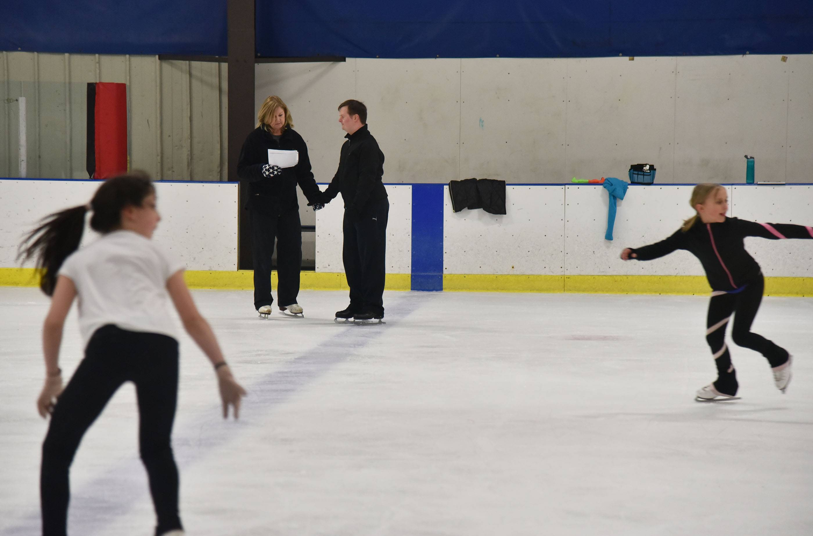 As others work on their routines, Coach Zane Shropshire talks with skater Ben Collins at the Crystal Ice House in Crystal Lake.
