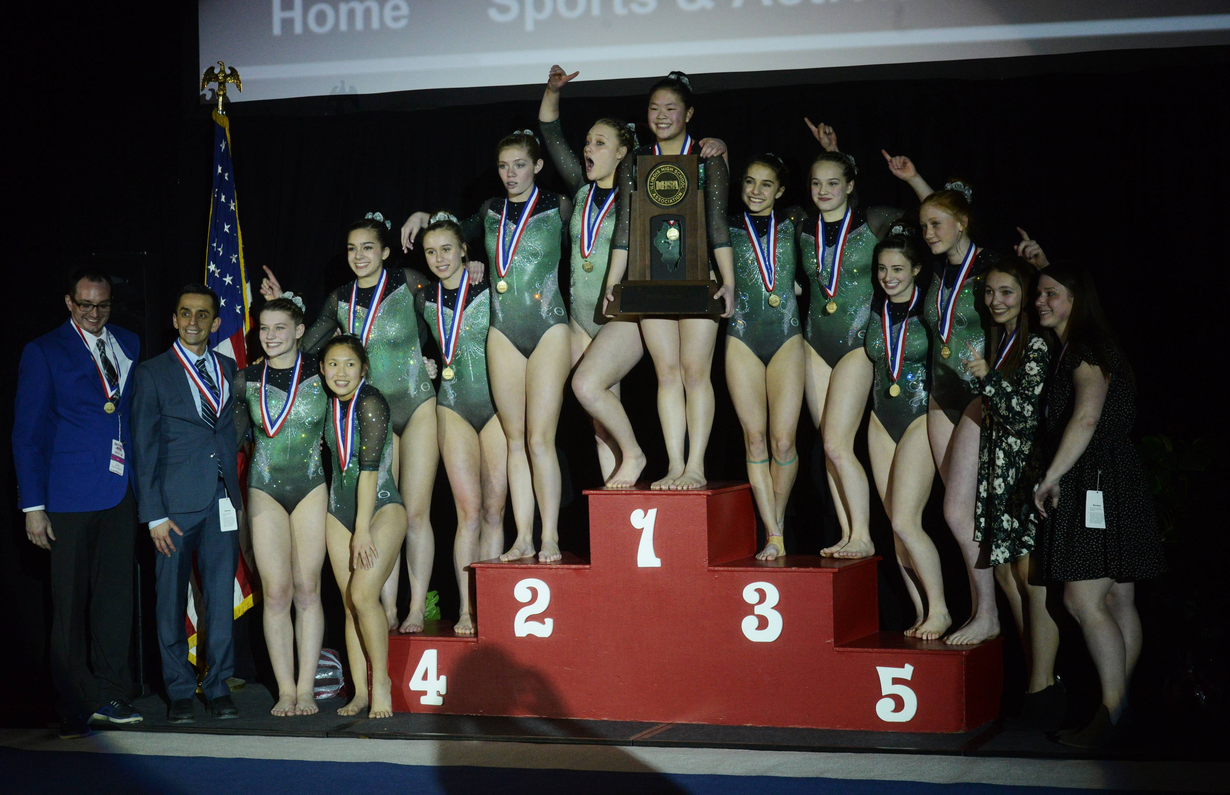 Glenbard West celebrates its first-place finish during the girls state gymnastics meet at Palatine High School Saturday.