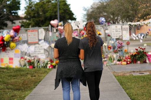 Sara Smith, left, and her daughter Karina Smith visit a makeshift memorial outside the Marjory Stoneman Douglas High School, where 17 students and faculty were killed in a mass shooting on Wednesday, in Parkland, Fla., Monday, Feb. 19, 2018. Nikolas Cruz, a former student, was charged with 17 counts of premeditated murder on Thursday.
