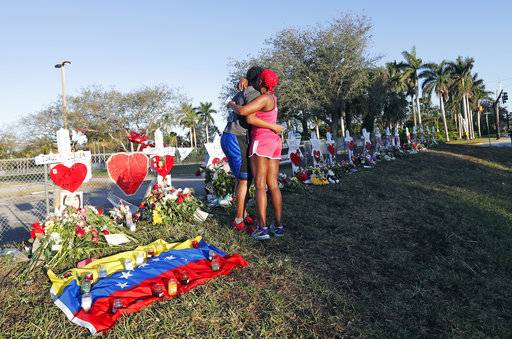 Denyse Christian, hugs her son Adin Christian, 16, a student at the school, at a makeshift memorial outside the Marjory Stoneman Douglas High School, where 17 students and faculty were killed in a mass shooting on Wednesday, in Parkland, Fla., Monday, Feb. 19, 2018. Nikolas Cruz, a former student, was charged with 17 counts of premeditated murder on Thursday.