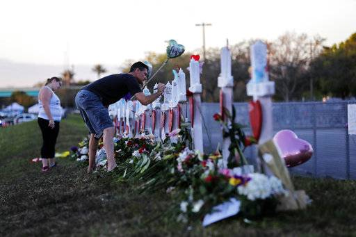 Paul Birmingham, a friend of the parents of victim Gina Montaldo, writes on a cross placed in her memory at a makeshift memorial outside the Marjory Stoneman Douglas High School, where 17 students and faculty were killed in a mass shooting on Wednesday, in Parkland, Fla., Monday, Feb. 19, 2018. Nikolas Cruz, a former student, was charged with 17 counts of premeditated murder on Thursday.