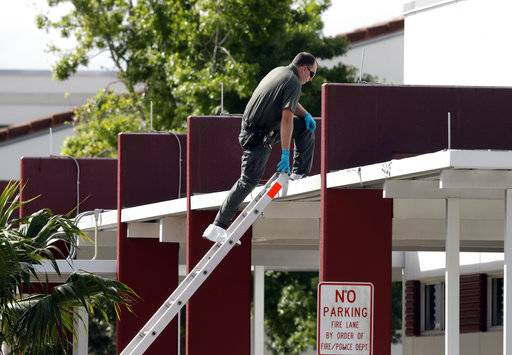 An investigator climbs to the roof of Marjory Stoneman Douglas High School, in Parkland, Fla., Monday, Feb. 19, 2018, where 17 students and faculty were killed in a mass shooting on Wednesday. Nikolas Cruz, a former student, was charged with 17 counts of premeditated murder on Thursday.