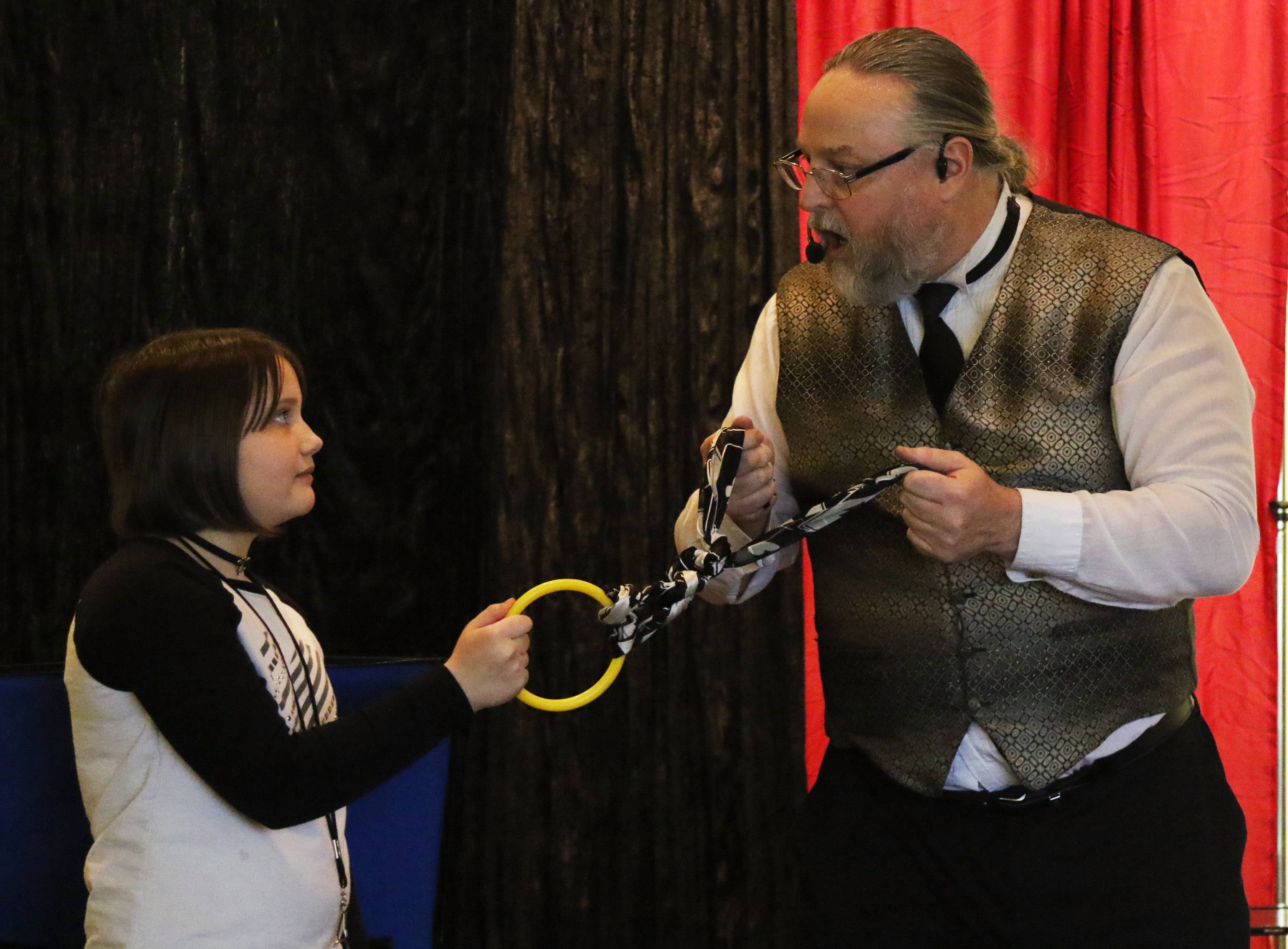Eleven-year-old Kelsey Nelson of Port Barrington helps magician Keith Cobb with a trick Monday at Wauconda Area Library. More than 120 patrons watched Cobb's show blending magic with comedy.
