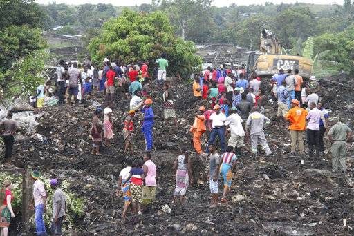 Rescuers search for survivors at the collapse of a garbage mound in Maputo, Mozambique, Monday, Feb. 19, 2018. Mozambican media say at least 17 people died when heavy rains triggered the partial collapse of the mound garbage. (AP Photo/Ferhat Momade)