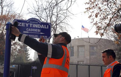 "An Ankara municipality worker fixes the new street sign, ""Olive Branch Street"" in Turkish, named after Turkey's military operation to drive out the Syrian Kurdish militia of an enclave in northwest Syria, in Ankara, Turkey, Monday, Feb. 19, 2018. Municipality workers on Monday took down the street sign for Nevzat Tandogan Street where the U.S. Embassy is located and replaced it with one that reads ""Olive Branch Street."" (AP Photo/Burhan Ozbilici)"