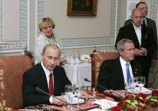 "FILE - In this Monday, July 19, 2006 file photo, Russian President Vladimir Putin, left, and U.S. President George W Bush attend a working dinner with the other leaders of the G8 nations, as Russian businessman Yevgeny Prigozhin stands on the right, in St. Petersburg, Russia. While Russian officials have denigrated a U.S. indictment charging 13 Russians with meddling in the 2016 U.S. presidential vote through an elaborate social media campaign, former Internet trolls employed at the same facility see them as well-grounded. The indictment alleged that Yevgeny Prigozhin _ a wealthy entrepreneur and restaurateur dubbed ""Putin's chef"" _ funneled money to set up the troll factory that sent operatives to the United States, created fictitious social media accounts and used them to spread tendentious messages. (Sergei Zhukov, Sputnik, Kremlin Pool Photo via AP, file)"