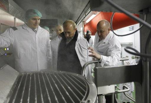 "In this pool photo taken on Monday, Sept. 20, 2010, businessman Yevgeny Prigozhin, right, shows Russian President Vladimir Putin, center, around his Concord Catering factory which produces school lunches, outside St. Petersburg, Russia. One of those indicted in the Russia probe is a businessman with ties to Russian President Vladimir Putin. Prigozhin is an entrepreneur from St. Petersburg who's been dubbed ""Putin's chef"" by Russian media. His restaurants and catering businesses have hosted the Kremlin leader's dinners with foreign dignitaries. (Alexei Druzhinin, Sputnik, Kremlin Pool Photo via AP)"