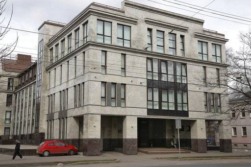 "FILE - In this file photo taken on Sunday, April 19, 2015, a women enters the four-storey building known as the ""troll factory"" in St. Petersburg, Russia.  The U.S. government allege the Internet Research Agency started interfering as early as 2014 in U.S. politics, extending to the 2016 presidential election, saying the agency was funded by a St. Petersburg businessman Yevgeny Prigozhin."