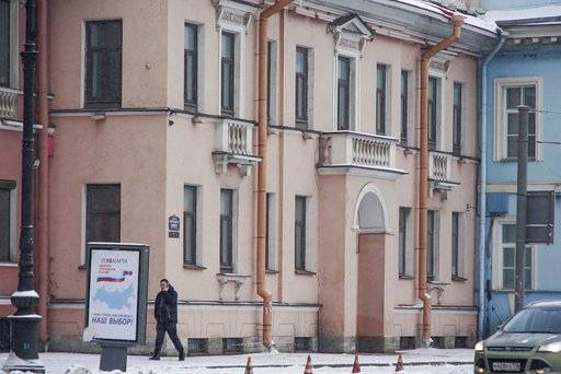 A security guard speaks on the phone outside the Concord Catering office in St. Petersburg, Russia, Sunday, Feb. 18, 2018.  The U.S. government allege the Internet Research Agency started interfering as early as 2014 in U.S. politics, extending to the 2016 presidential election, saying the agency was funded by a St. Petersburg businessman Yevgeny Prigozhin.