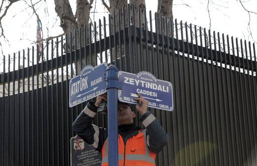 "An Ankara municipality worker fixes the new street sign, ""Olive Branch Street"" in Turkish, named after Turkey's military operation to drive out the Syrian Kurdish militia of an enclave in northwest Syria, in Ankara, Turkey, Monday, Feb. 19, 2018. Municipality workers on Monday took down the street sign for Nevzat Tandogan Street where the U.S. Embassy is located and replaced it with one that reads ""Olive Branch Street."" The Embassy's flag was at half-staff in respect for the Florida school shooting victims."