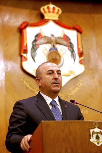 "Turkish Foreign Minister Mevlut Cavusoglu, and Jordanian Foreign Minister Ayman Safadi, give a press conference in Amman, Jordan, Monday, Feb. 19, 2018. Cavusoglu said his country is ready to battle Syrian government troops if they enter an enclave in northern Syria to protect Syrian Kurdish fighters. Syrian state media said Sunday that pro-Syrian government forces will begin entering the Afrin enclave ""within hours,"" after reaching an agreement with the Kurdish militia in control of the region."