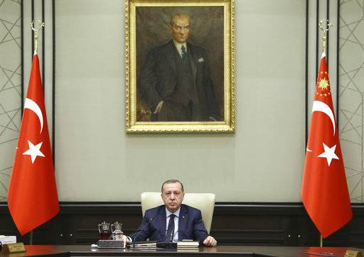 "Backdropped by a picture of modern Turkey's founder Mustafa Kemal Ataturk, Turkey's President Recep Tayyip Erdogan chairs a cabinet meeting in Ankara, Turkey, Monday, Feb. 19, 2018. Turkish officials say Erdogan held a telephone conversation with his Russian counterpart Vladimir Putin on Monday, during which the two reaffirmed their determination to cooperate and act in coordination in the fight against ""terrorism"" in Syria. The two leaders spoke as Syrian state media reported that pro-Syrian government forces will begin entering Afrin. (Kayhan Ozer/Pool Photo via AP)"