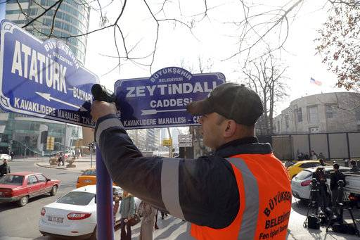 "An Ankara municipality worker fixes the new street sign, ""Olive Branch Street"" in Turkish, named after Turkey's military operation to drive out the Syrian Kurdish militia of an enclave in northwest Syria, in Ankara, Turkey, Monday, Feb. 19, 2018. Municipality workers on Monday took down the street sign for Nevzat Tandogan Street where the U.S. Embassy is located and replaced it with one that reads ""Olive Branch Street."""