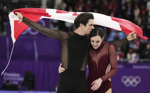 Tessa Virtue and Scott Moir of Canada celebrate during the venue ceremony after winning the gold medal in the ice dance, free dance figure skating final in the Gangneung Ice Arena at the 2018 Winter Olympics in Gangneung, South Korea, Tuesday, Feb. 20, 2018. (AP Photo/Julie Jacobson)