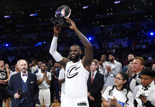 Team LeBron's LeBron James, of the Cleveland Cavaliers, holds the MVP trophy after his team defeated Team Stephen at the NBA All-Star basketball game, Sunday, Feb. 18, 2018, in Los Angeles. Team LeBron won 148-145. (AP Photo/Chris Pizzello)