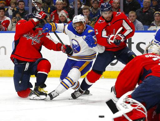 Buffalo Sabres Evander Kane, center, battles Washington Capitals Alex Ovechkin, left, and Matt Niskanen, right, during the second period of an NHL hockey game, Monday, Feb. 19, 2018, in Buffalo, N.Y. (AP Photo/Jeffrey T. Barnes)