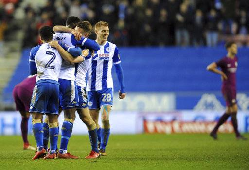 Wigan Athletic players celebrate at the end of the English FA Cup fifth round soccer match between Wigan Athletic and Manchester City at The DW Stadium, Wigan, England, Monday, Feb. 19, 2018. Wigan Athletic won the game 1-0. (AP Photo/Rui Vieira)