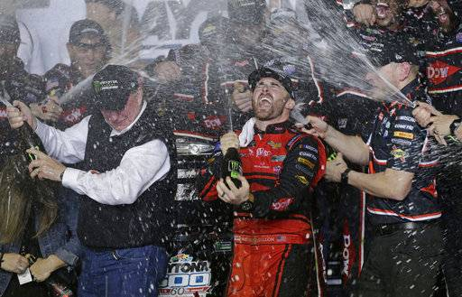 Austin Dillon, center, celebrates with his team and his grandfather, Richard Childress, left, in Victory Lane after winning the NASCAR Daytona 500 Cup series auto race at Daytona International Speedway in Daytona Beach, Fla., Sunday, Feb. 18, 2018. (AP Photo/Terry Renna)