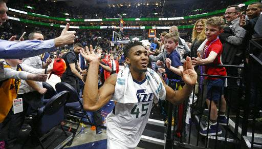 FILE - In this Feb. 12, 2018, file photo, Utah Jazz guard Donovan Mitchell (45) celebrates as he runs off the court following their NBA basketball game against the San Antonio Spurs, in Salt Lake City. As the season picks back up following the All-Star break, the Jazz are riding an 11-game winning streak. They're currently part of a tightly-clustered group Western Conference teams that are vying for playoff position with some two months left in the regular season. (AP Photo/Rick Bowmer, File)