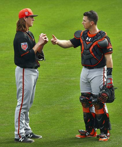 San Francisco Giants' Buster Posey, right, speaks with pitcher Tyler Herb during a spring training baseball practice on Thursday, Feb. 15, 2018 in Scottsdale, Ariz. (AP Photo/Ben Margot)