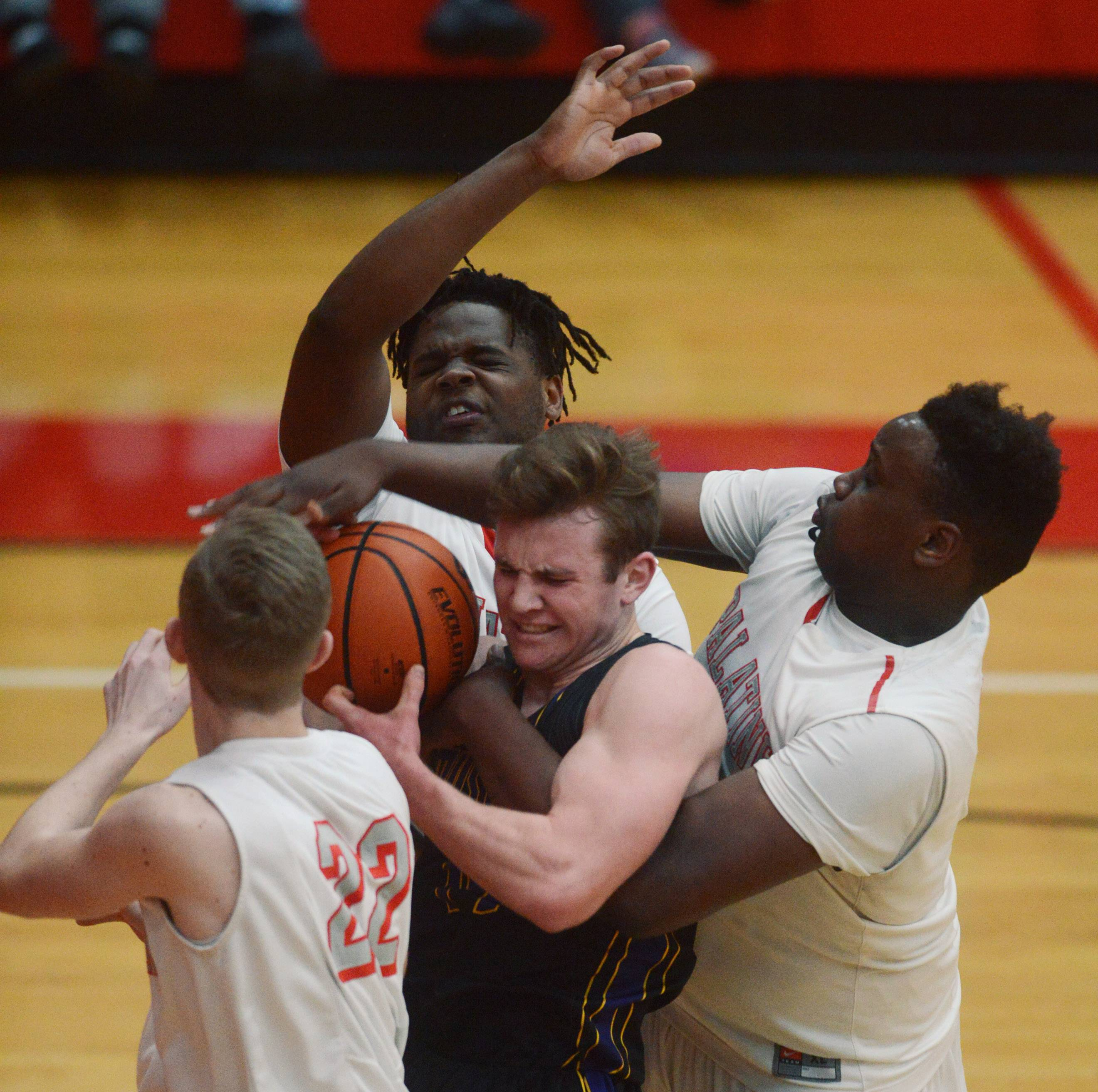 From left, Palatine's Ben Storm, David Balanganayi and Julian Campbell surround Rolling Meadows' Sean Nolan under the Mustangs' basket during Tuesday's game at Palatine.