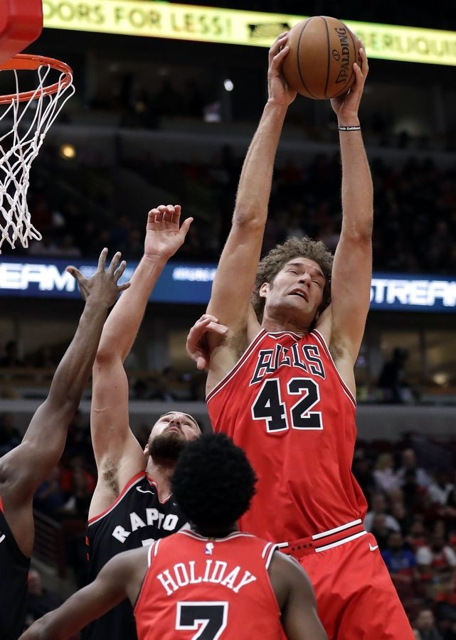 Chicago Bulls center Robin Lopez, right, rebounds a ball against Toronto Raptors center Jonas Valanciunas during the first half of an NBA basketball game Wednesday, Feb. 14, 2018, in Chicago.
