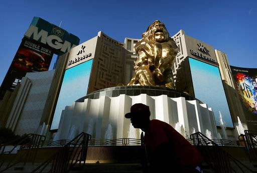 FILE - In this Aug. 3, 2015, file photo, a man rides his bike past the MGM Grand hotel and casino in Las Vegas. MGM Resorts International reports financial results Tuesday, Feb. 20, 2018. (AP Photo/John Locher, File)
