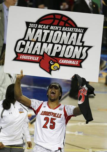 FILE - In this April 8, 2013, file photo, Louisville center Zach Price (25) holds signage after Louisville defeated Michigan 82-76 in the NCAA Final Four tournament college basketball championship game, in Atlanta. Louisville must vacate its 2013 men's basketball title following an NCAA appeals panel's decision to uphold sanctions against the men's program for violations committed in a sex scandal. The Cardinals will have to vacate 123 victories including the championship, and return millions in postseason revenue. The decision announced on Tuesday, Feb. 20, 2018, by the governing body's Infraction Appeals Committee ruled that the NCAA has the authority to take away championships for what it considers major rule violations. (AP Photo/Chris O'Meara, File)