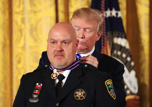 President Donald Trump awards public safety Medal of Valor to Lt. William Buchanan of the Avery County, N.C. Sheriff's Office, during a ceremony in the East Room of the White House, Tuesday, Feb. 20, 2018, in Washington. (AP Photo/Manuel Balce Ceneta)