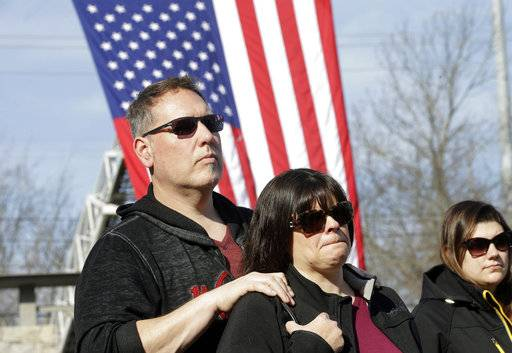 Jeff Pelchat, of Rehoboth, Mass., left, places his hands on the shoulders of his wife, Station nightclub fire survivor Kathy Pelchat, also of Rehoboth, center, during a ceremony Tuesday, Feb. 20, 2018, to mark the 15th anniversary of the fire, in West Warwick, R.I. The Feb. 20, 2003, fire at the nightclub in West Warwick, that killed 100 and injured more than 200 others, started when pyrotechnics for the rock band Great White set fire to flammable foam installed as soundproofing. The site of the fire is now a memorial park. (AP Photo/Steven Senne)