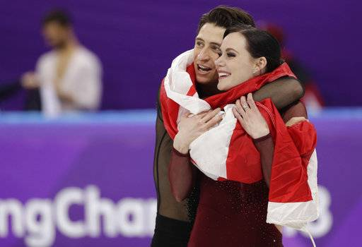 Tessa Virtue and Scott Moir of Canada celebrate during the venue ceremony after winning the gold medal in the ice dance, free dance figure skating final in the Gangneung Ice Arena at the 2018 Winter Olympics in Gangneung, South Korea, Tuesday, Feb. 20, 2018. (AP Photo/David J. Phillip)