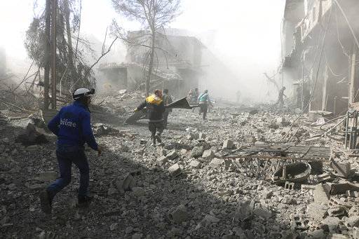In this photo released on Tuesday Feb. 20, 2018 which provided by the Syrian Civil Defense group known as the White Helmets, shows members of the Syrian Civil Defense run to help survivors from a street that attacked by airstrikes and shelling of the Syrian government forces, in Ghouta, suburb of Damascus, Syria. A Syrian monitoring group and paramedics say government shelling and airstrikes on rebel-held suburbs of the capital, Damascus, killed at least 98 people on Monday. (Syrian Civil Defense White Helmets via AP)