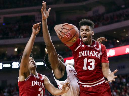 Indiana's Juwan Morgan (13) and Justin Smith (3) and Nebraska's Jordy Tshimanga, center, vie for a rebound, won by Morgan, during the first half of an NCAA college basketball game in Lincoln, Neb., Tuesday, Feb. 20, 2018. (AP Photo/Nati Harnik)