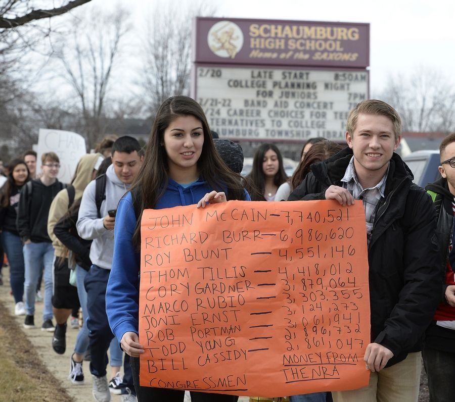 Schaumburg High School seniors Lexi Espino, 18, and Kenny Beymer, 18, carry a sign Wednesday while participating in a school walkout to advocate for more gun control measures.