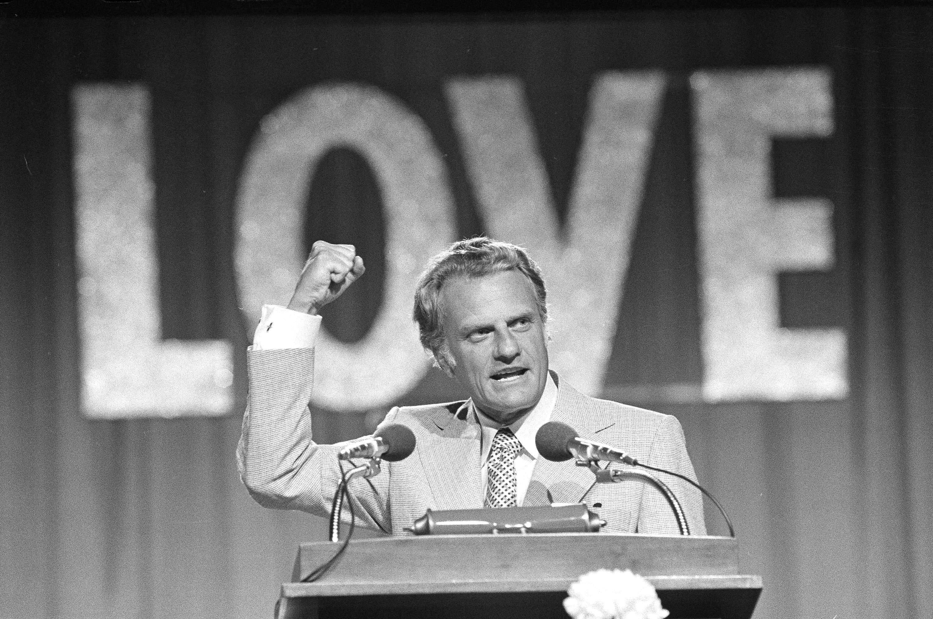 "Rev. Billy Graham speaks to 18,000 followers on June 13, 1974, in Dallas on the closing night of the Southern Baptist Convention. The theme of the convention was ""Share His Love Now."""
