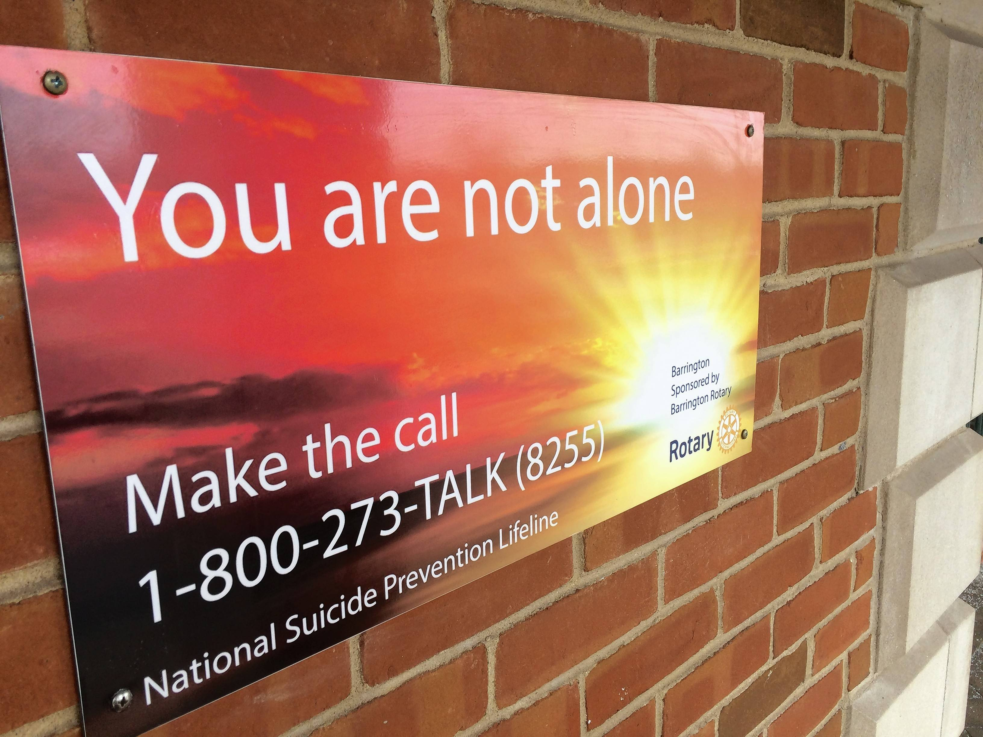 Signs like this one attached to an outside wall of Barrington's Metra station are going up at stops along the Union Pacific Northwest Line in an effort to encourage people in need to seek help. Barrington's Rotary clubs are behind the initiative.