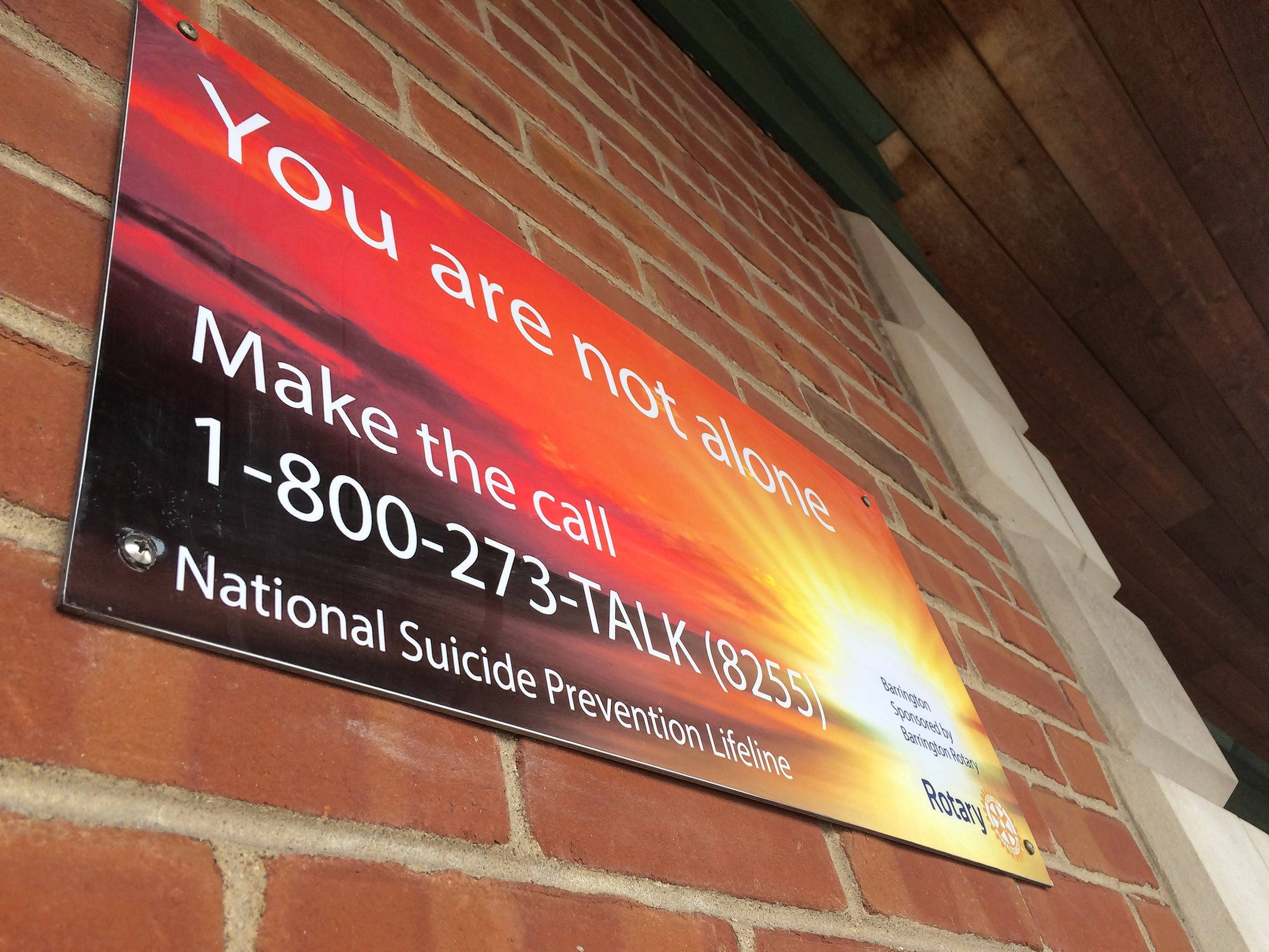 This sign attached to an outside wall of Barrington's Metra station near the train platform offers a way to find help as part of a suicide prevention effort along the Union Pacific Northwest Line. Barrington's Rotary clubs are behind the initiative.