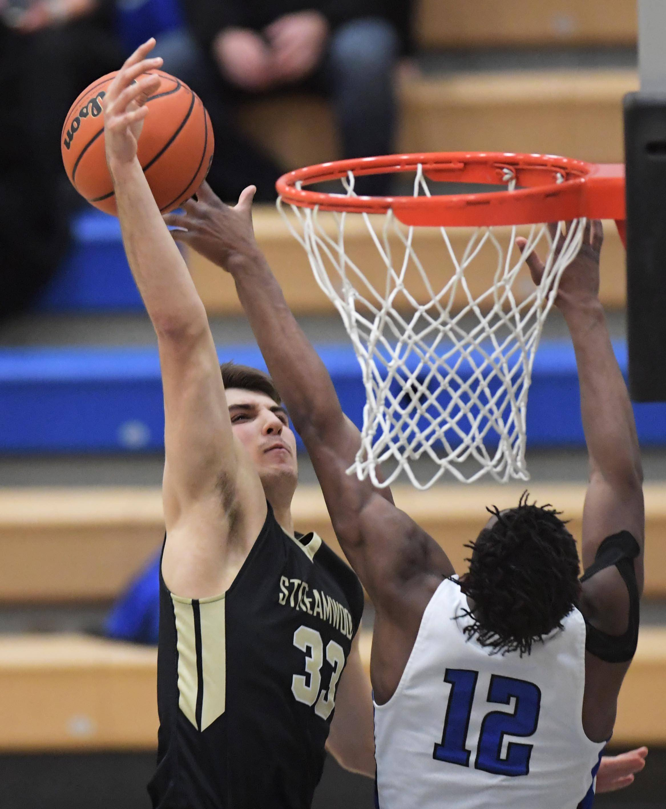 St. Charles North's Tyler Nubin blocks a shot by Streamwood's Brendon Marton Wednesday in a boys basketball game in St. Charles.